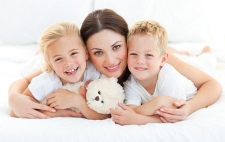 Animated siblings with their mother lying on a bed Stock Photo - 10092232