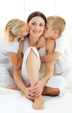 Cute siblings kissing their mother sitting on a bed  Stock Photo - 10093233