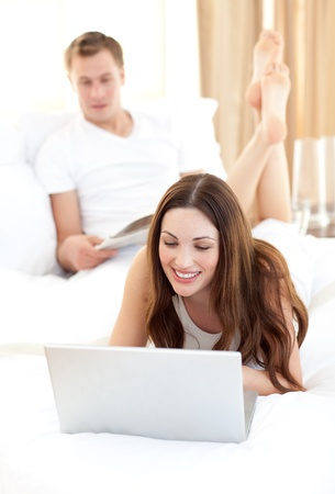 Beautiful woman with her husband working at a laptop photo