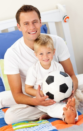 mirthful: Close-up of a little boy and his father playing with a soccer ball