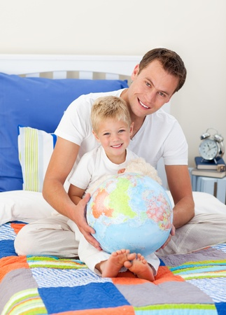 Smiling father and his son looking at a terretrial globe photo