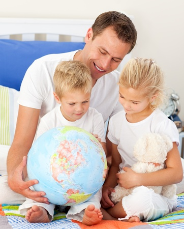 Adorable children and their father looking at a terrestrial globe photo