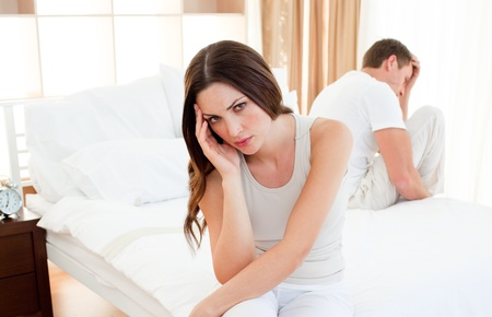 Upset couple sitting separately on their bed Stock Photo - 10091972
