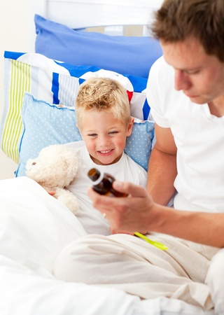Caring man looking after his sick son photo
