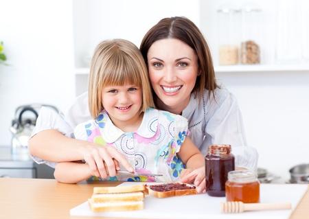 familia comiendo: Ni�a rubia y su madre preparar tostadas