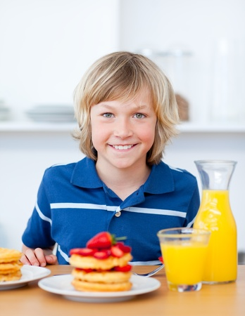 Smiling boy eating waffles with strawberries photo