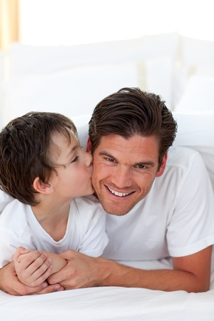 Little boy kissing his father lying on bed photo