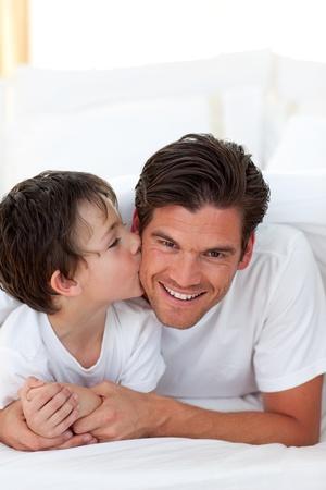 otec: Malý chlapec líbat jeho otec ležící na posteli