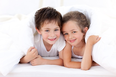Brother and sister playing on parents bed photo