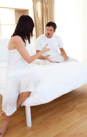 Couple on bed having a row photo