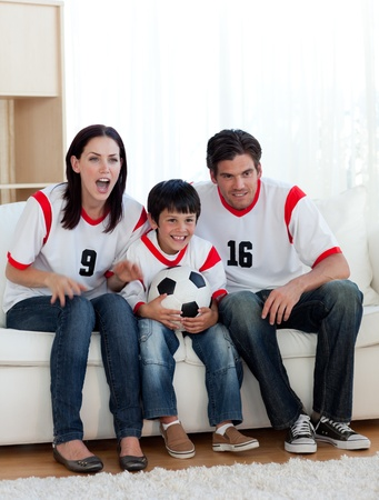 Parents and their son watching a football match photo