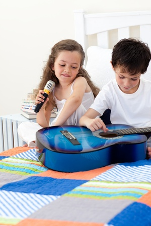 Brother and sister having fun with a guitar photo