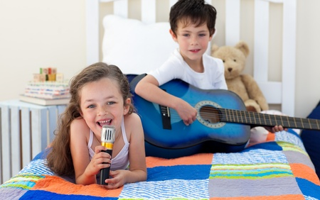 Little boy playing guitar and his sister singing Stock Photo - 10110793