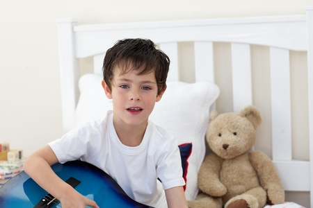 boy playing guitar: Little boy singing and playing guitar Stock Photo