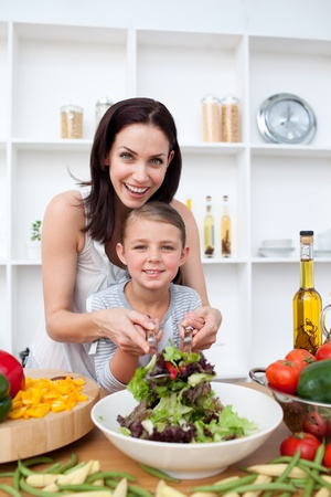 Happy mother and her girl preparing a salad photo