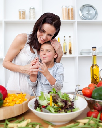 Litlle girl and her mother preparing a salad  photo