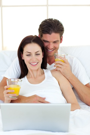 Lovers using a laptop on their bed Stock Photo - 10106695