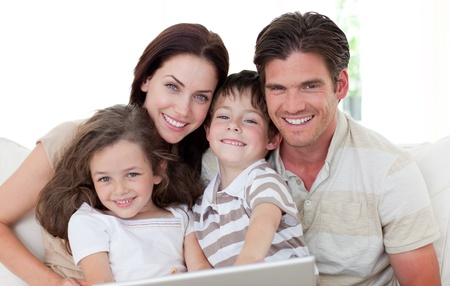 Smiling family using a laptop photo