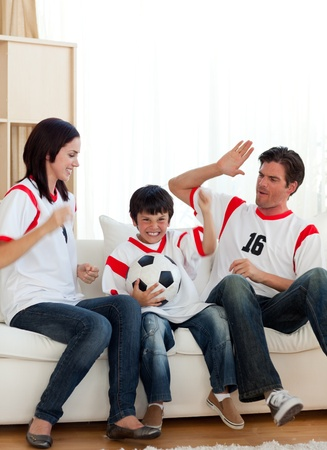 Joyful family watching football match photo