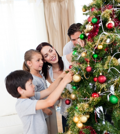 decorating christmas tree: Happy family decorating a Christmas tree with boubles