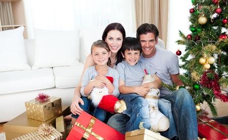 Familia feliz celebración de montones de regalos en Navidad Foto de archivo