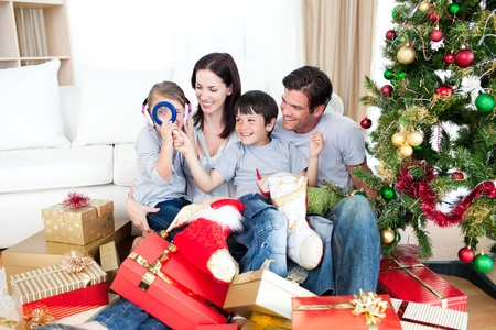 Happy family having fun with Christmas presents photo