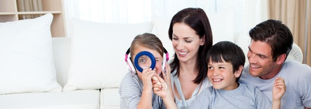 Happy family playing with a magnifying glass