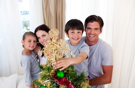 Happy little kid decorating a Christmas tree with his family photo