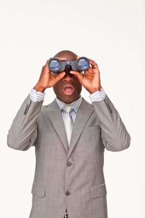 Surprised Afro-American businessman looking through binoculars photo