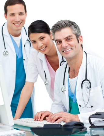 Smiling doctors and nurse working at computer photo