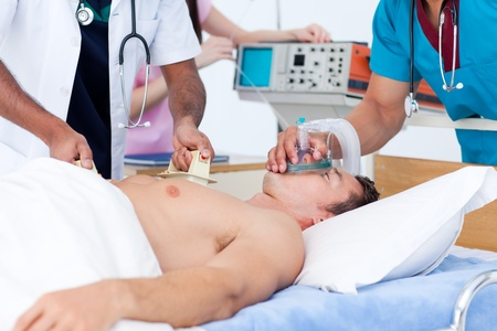 defibrillator: Concentrated medical team resuscitating a patient Stock Photo
