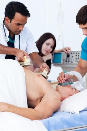 defibrillator: A diverse medical team resuscitating a patient Stock Photo