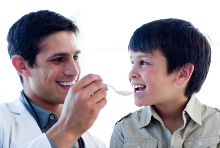 Self-assured doctor giving medicine to a little boy Stock Photo - 10106704