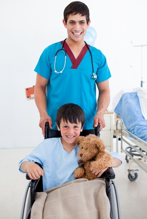 paraplegic: Portrait of a cute little boy sitting on wheelchair and a doctor