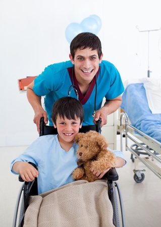 Portrait of a little boy sitting on wheelchair and a doctor photo