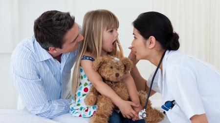 Doctor examining childs throat photo