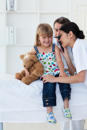 Serious patient examing littl girl's ears Stock Photo - 10110191