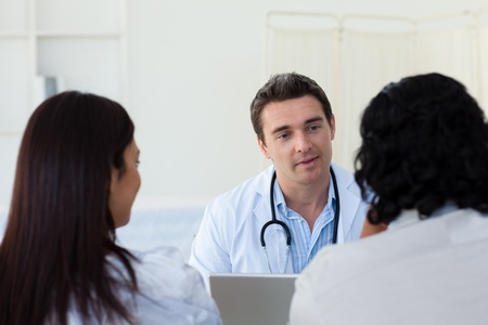 Male doctor explaining diagnosis to a couple photo
