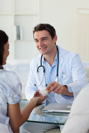 prescribe: Male doctor giving pills to a female patient Stock Photo
