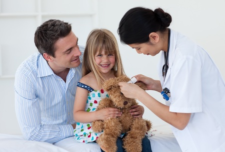 Smiling patient examining a teddy bear with a doctor photo