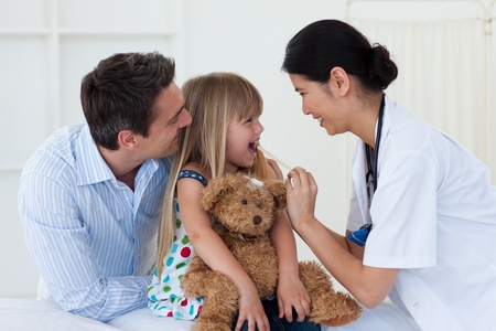 Female doctor checking her patients throat photo
