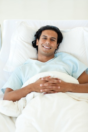 Portrait of a smiling patient lying in a hospital bed photo