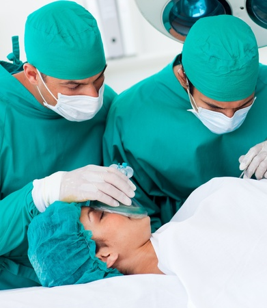 Close-up of surgeons near patient lying on operating table photo