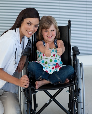 knees up: Portrait of a little girl on a wheelchair with her doctor