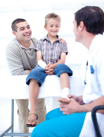 Doctor bandaging a patient's foot with his father Stock Photo - 10107025
