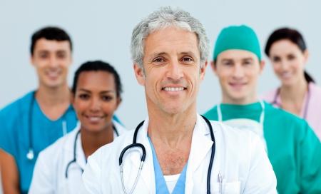 Senior arts staande in de voorkant van zijn team Stockfoto