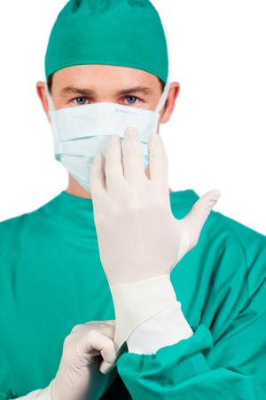 surgical mask: Young surgeon putting his glover