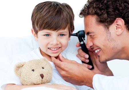 otoscope: Attractive doctor examining patients ears Stock Photo