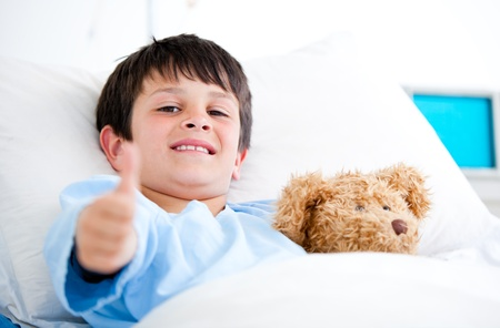 enfant malade: Petit gar�on serrant un ours en peluche couch� dans un lit d'h�pital