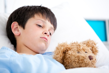 sick teddy bear: Portrait of a sick boy lying in a hospital bed